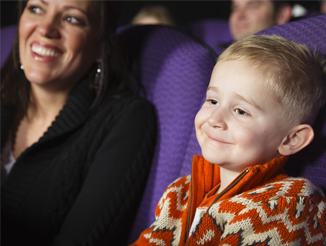 A mother and son watching a planetarium showing
